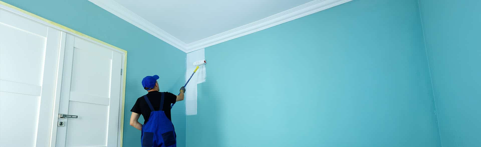 a cypress painter painting an apartment wall blue