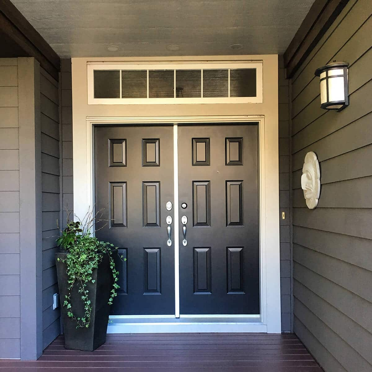 a double door painted in black with golden handles by cypress painting