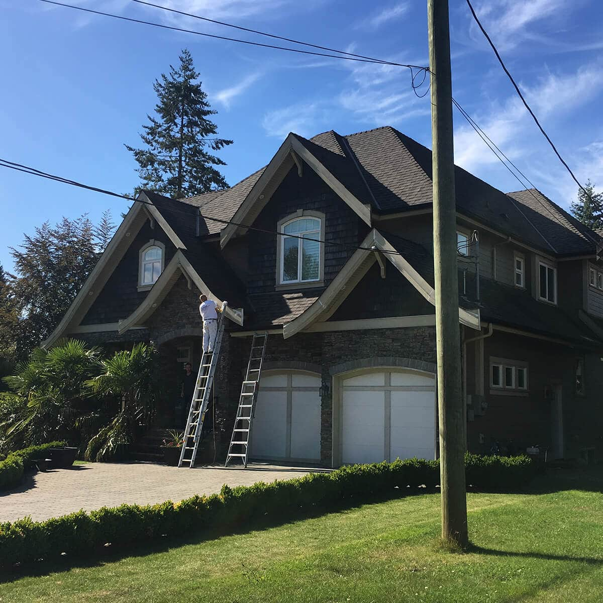 A cypress painter painting the exterior of a residential house
